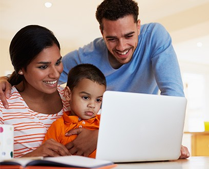 family looking at laptop at home